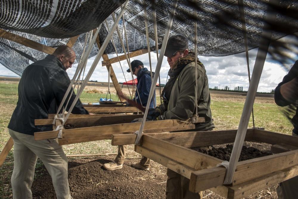 Mit Mitarbeiter der DPAA sieben und zerkleinern die Erde aus der Grabungsstelle auf der Suche nach kleinsten Resten.